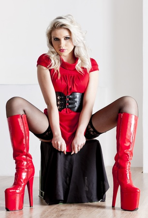 sitting young woman wearing extravagant boots photo