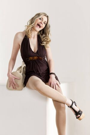 sitting woman wearing summer clothes and shoes with a handbag photo