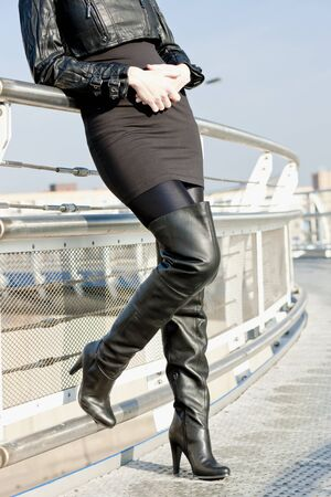 detail of standing woman wearing fashionable black boots photo