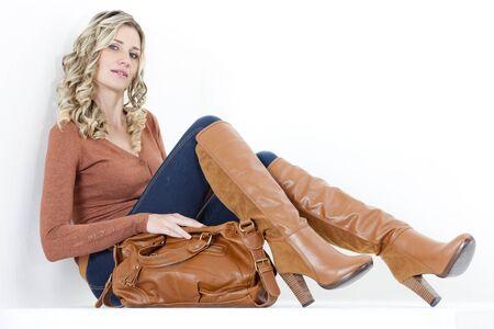 fair woman: sitting woman wearing fashionable brown boots with a handbag