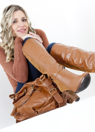 jeans boots: portrait of sitting woman wearing fashionable brown boots with a handbag