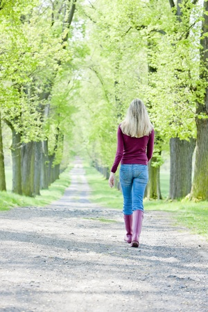 woman wearing rubber boots in spring alley photo