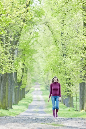 woman wearing rubber boots walking in spring alley photo