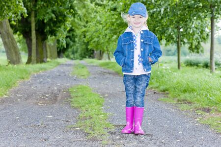little girl wearing rubber boots in spring alley Stock Photo - 12099628
