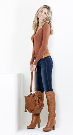 jeans boots: standing woman wearing fashionable brown boots with a handbag