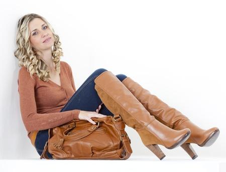 botas: mujer sentada vestida de moda las botas de color marr�n con un bolso de mano