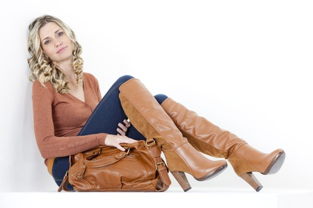 women in jeans: sitting woman wearing fashionable brown boots with a handbag