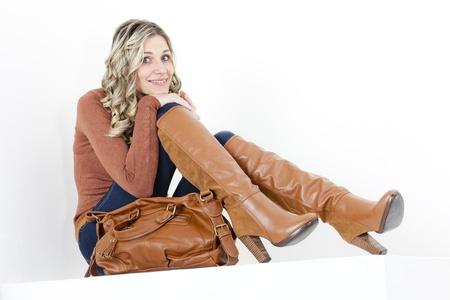 mujeres sentadas: mujer sentada vestida de moda las botas de color marrón con un bolso de mano