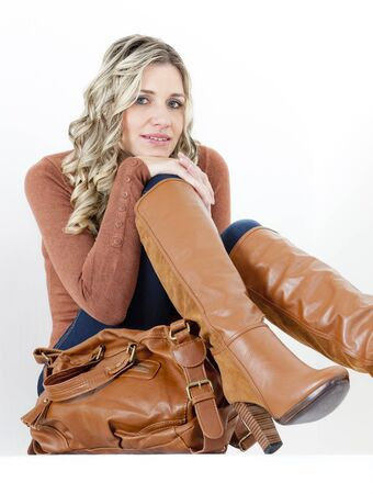 portrait of sitting woman wearing fashionable brown boots with a handbag photo