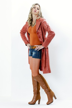 standing woman wearing fashionable brown boots and coat photo