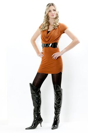 standing woman wearing dress and fashionable black boots Stock Photo