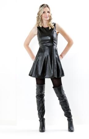 staande vrouw draagt zwarte jurk en zwarte laarzen