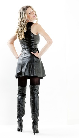 standing woman wearing black dress and black boots photo