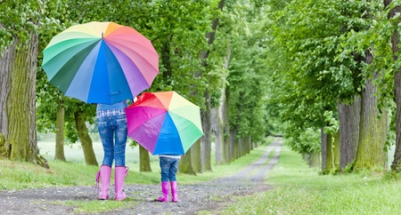 mother and her daughter with umbrellas in spring alley photo