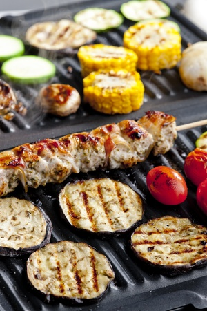 meat skewer and vegetables on electric grill photo