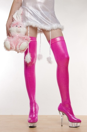 extravagant pink boots and hand holding a rabbit toy photo