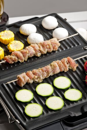 meat skewers and vegetables on electric grill photo