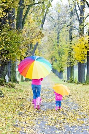 mère et sa fille avec des parasols en automne allée