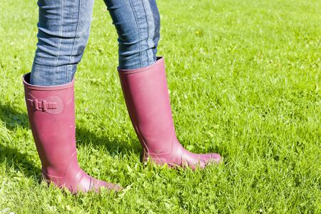 detail of woman wearing rubber boots on lawn photo
