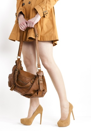 detail of standing woman wearing coat and brown pumps with a handbag Foto de archivo
