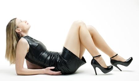woman lying down: lying woman wearing black dress and shoes Stock Photo