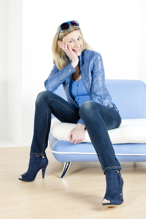 women jeans: woman wearing blue clothes sitting on sofa