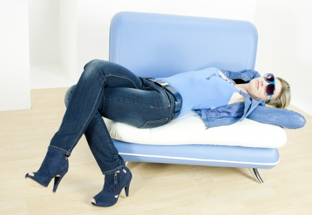 woman wearing blue clothes lying on sofa Stock Photo - 13676730