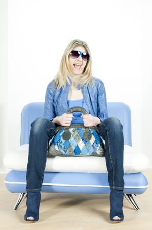 woman wearing blue clothes with handbag sitting on sofa Stock Photo - 13676735