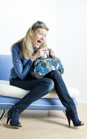 woman wearing blue clothes with handbag sitting on sofa Stock Photo - 13676729