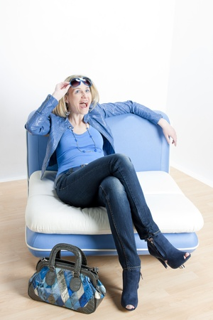 woman wearing blue clothes with handbag sitting on sofa photo