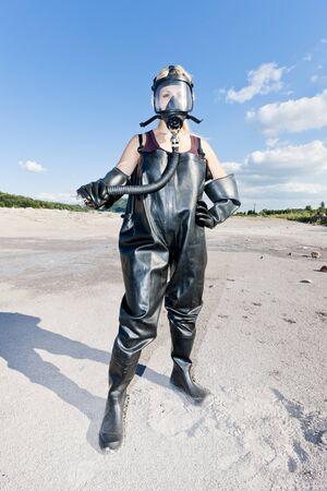 gasmask: donna in piedi con la maschera antigas indossare indumenti protettivi