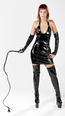 woman wearing extravagant clothes holding a whip