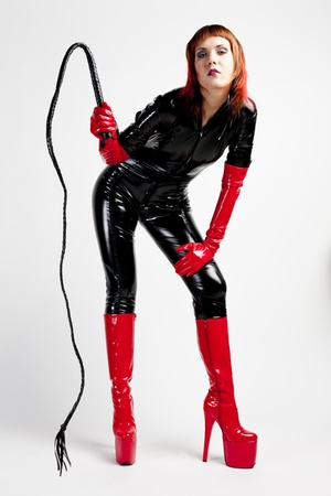 standing woman wearing extravagant clothes holding a whip Stock Photo