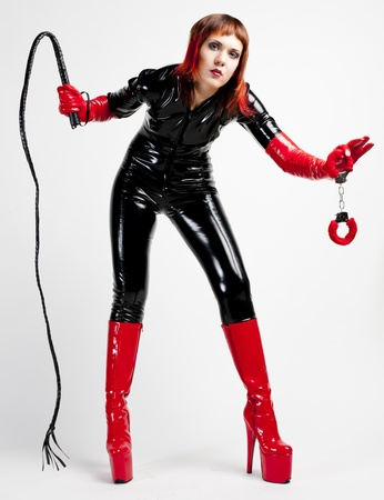 dominance: standing woman wearing extravagant clothes holding a whip and handcuffs