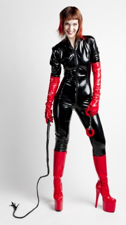 latex: standing woman wearing extravagant clothes holding a whip and handcuffs