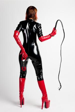 femme debout portant des vêtements extravagants tenant un fouet et des menottes