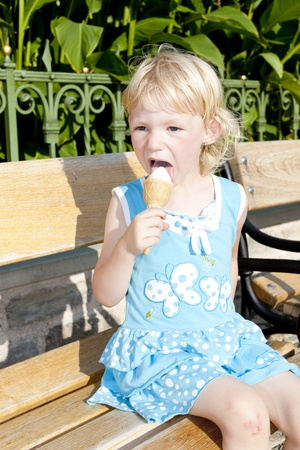 little girl with ice cream sitting on bench photo