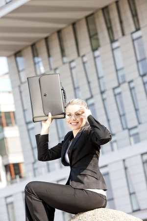 sitting young businesswoman with a briefcase photo