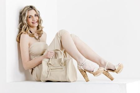 femme assise portant des vêtements d'été et des chaussures avec un sac à main