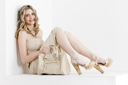 sitting woman wearing summer clothes and shoes with a handbag