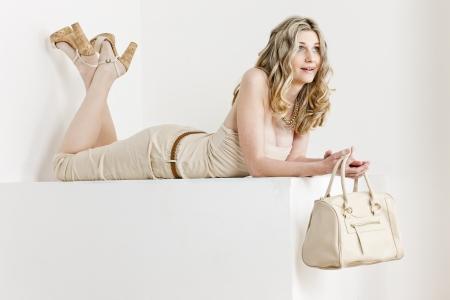 pantalones abajo: mujer acostada con ropa de verano y zapatos con un bolso de mano Foto de archivo