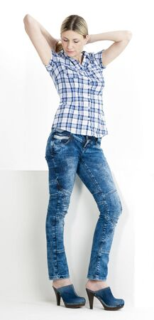 standing woman wearing jeans and denim clogs photo