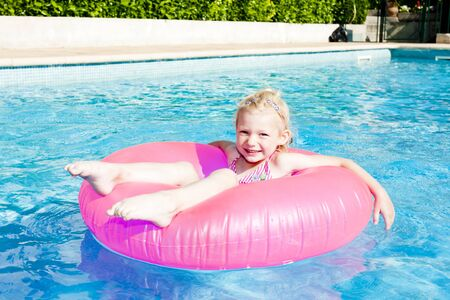 little girl with rubber ring in swimming pool photo