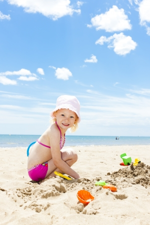 bucket and spade: little girl playing on the beach at sea Stock Photo