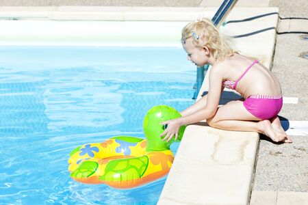 little girl with rubber ring at swimming pool photo
