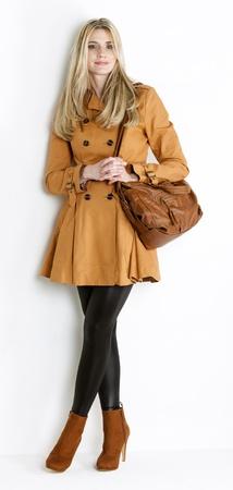 manteau de femme debout portant et à la mode des chaussures marron avec un sac à main Banque d'images