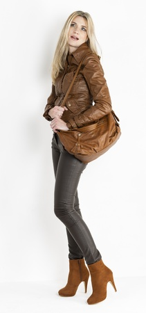 long pants: standing woman wearing brown clothes and fashionable brown shoes with a handbag