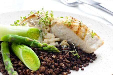 cooked fish: butterfish with green lentils, leek and green asparagus Stock Photo