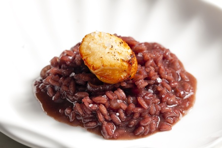fried Saint Jacques mollusc on risotto steamed with red wine photo