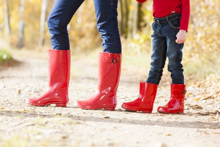 detail of mother and daughter wearing rubber boots photo